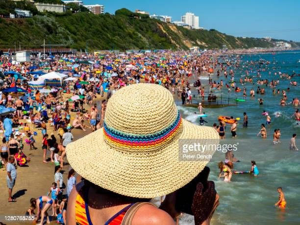 Woman checks her phone overlooking a crowded Bournemouth beach on June 25,2020 in Bournemouth, England. A major incident was declared after thousands...