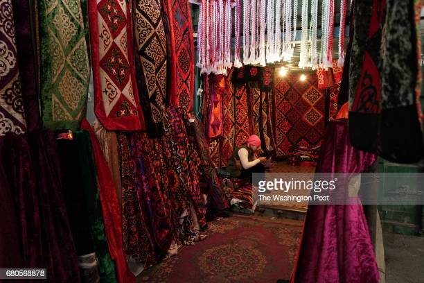 APRIL 28 A woman checks her smart phone in a stall selling traditional rugs in the sprawling bazaar in KaraSuu on Kyrgyzstan's border with Uzbekistan...
