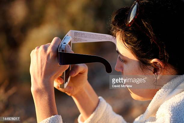 Woman checks her smart phone while watching the first annular eclipse seen in the U.S. Since 1994 with special glasses to protect her eyes on May 20,...