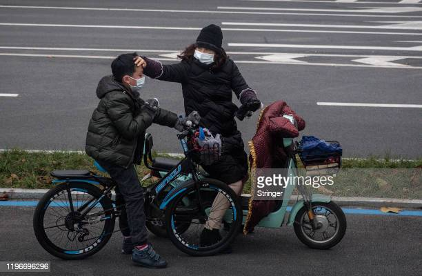 Woman checks her son's forehead on January 27, 2020 in Wuhan, China. As the death toll from the coronavirus reaches 80 in China with over 2700...