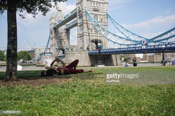 A woman checks her watch as a man reads his book in Tower bridge of London UK Thursday 26 July 2018