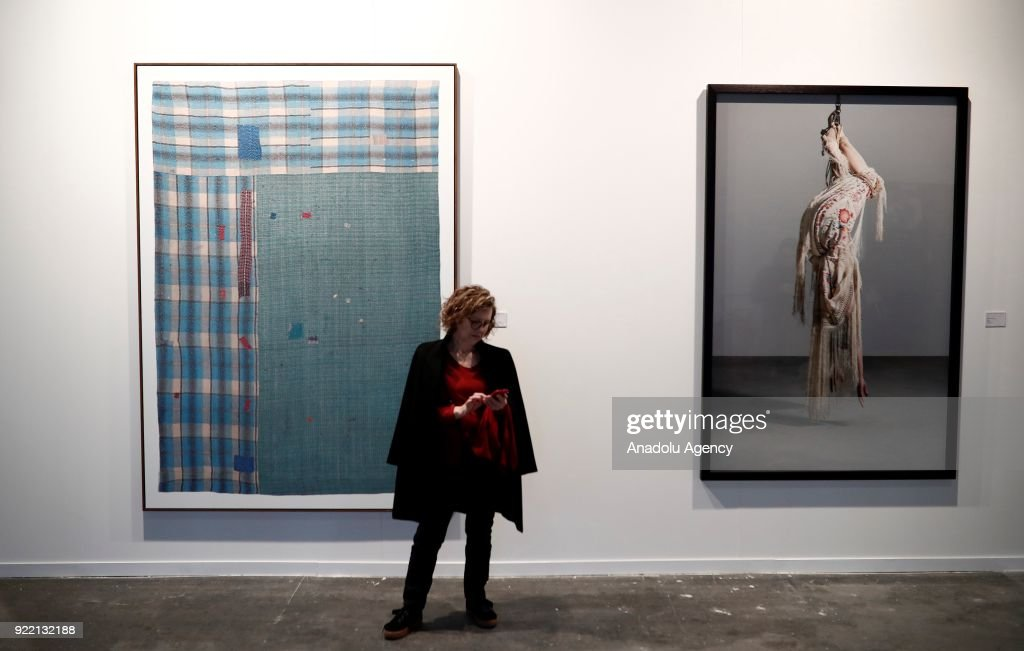 A woman checks his phone in front of artworks during ARCOmadrid 2018 in Madrid, Spain on February 21, 2018.