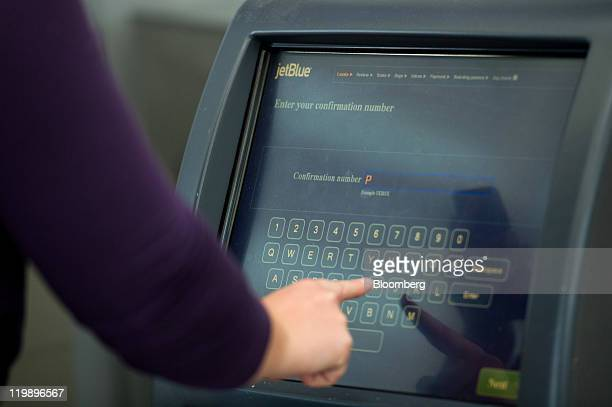 A woman checks in at a selfservice kiosk at the JetBlue Airways Corp checkin counter at the San Francisco International Airport in San Francisco...