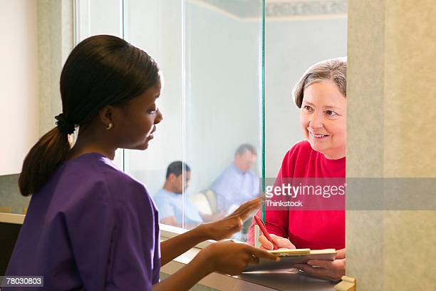A woman checks in to the doctor's office with the nurse at the window, while other patients wait in the background