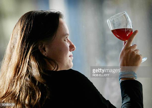 A woman checks out a glass of wine in Sydney 22 April 2005 as Australian beverages giant Foster's Group increased its takeover bid for Southcorp by...