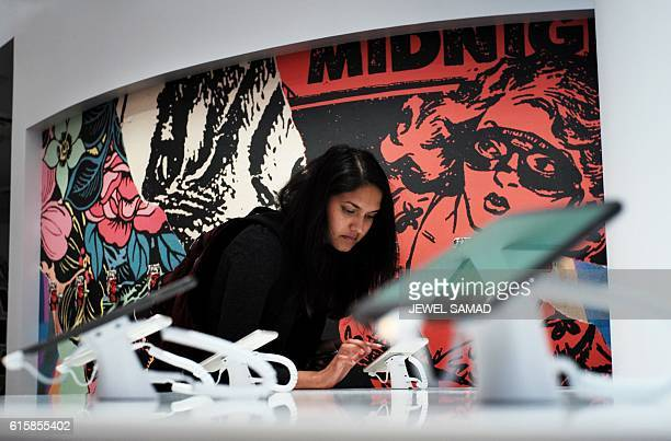 A woman checks out a Google phone after the opening of Google's popup store in New York on October 20 2016 Google opened its first retail store which...