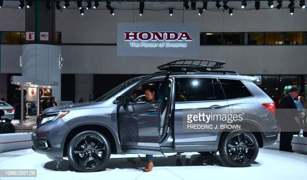 Woman checks out the drivers side of a 2019 Honda Passport AWD Elite on display at AutoMobility LA, the trade show ahead of the LA Auto Show, on...