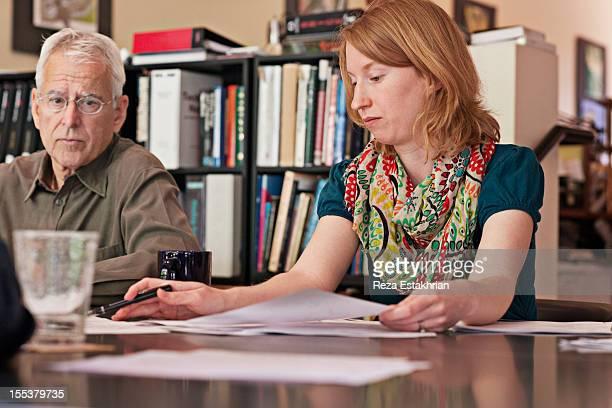 Woman checks paperwork during meeting