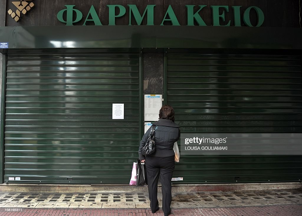 A woman checks pharmacies on duty list at a shut down pharmacy in Athens on December 11, 2012 during a 24 hours pharmacists strike. Pharmacists called for a 24-hour strike to demand the payment of debts owed by the National Organization for Healthcare Provision and against the ministry threat to fully liberalize their sector, which would mean many losing out on privileged trading conditions. Pharmacists are refusing to give medicines on credit to customers insured with National Organization for Healthcare Provision until all debts have been settled..