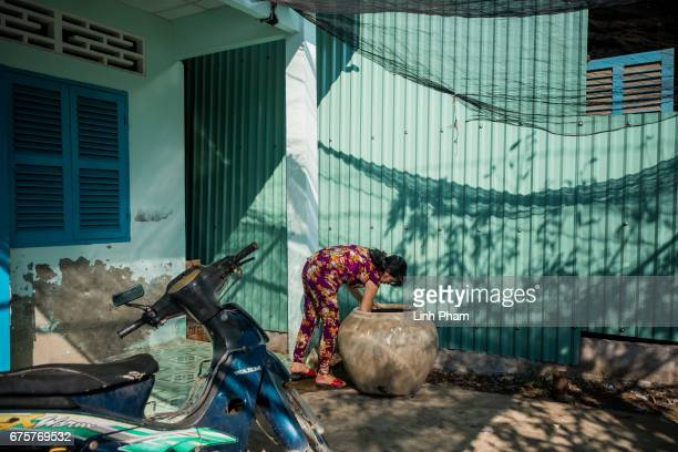 A woman checks the fresh water she just bought on April 28 2017 in Thua Duc Village Binh Dai District Ben Tre Province Vietnam Due to the lack of...