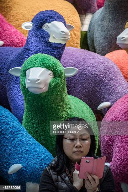 A woman checks the pictures she took in front in front of a multi coloured sheep installation displayed in a shopping mall for the Chinese New Year...