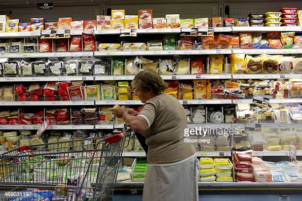 A woman checks the price of an item at a grocery store in Buenos Aires Argentina on Wednesday Feb 12 2014 Foreignexchange reserves are emerging as...