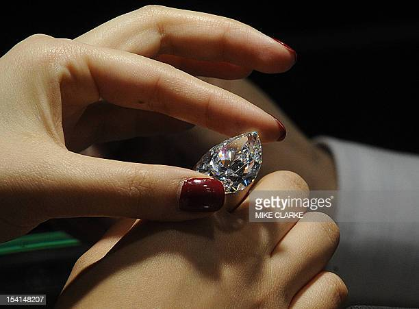 A woman checks the quality of a diamond at the Hong Kong Jewellery and Gem Fair in Hong Kong on September 22 2009 The seven day event which began on...