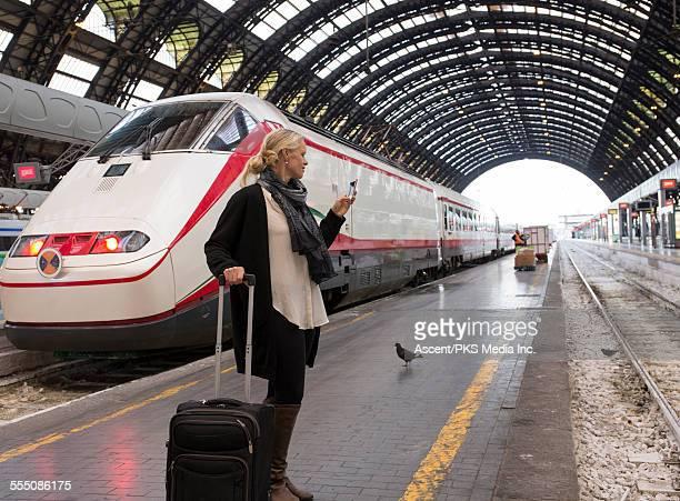 Woman checks timetable on phone, train platform