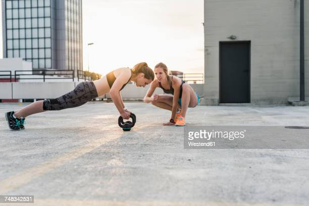 woman cheering at training partner kettlebell on parking level in the city - fair play sport foto e immagini stock