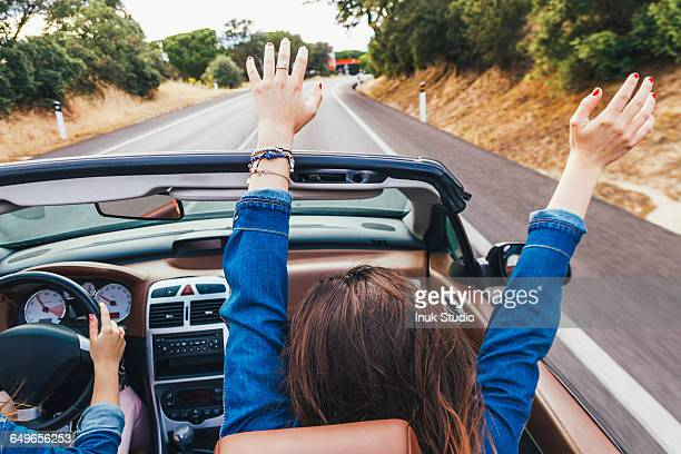 Woman cheering in convertible