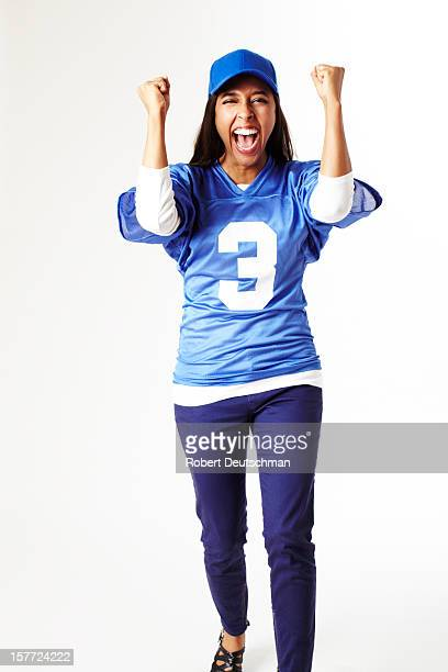 Woman cheering in sports jersey.