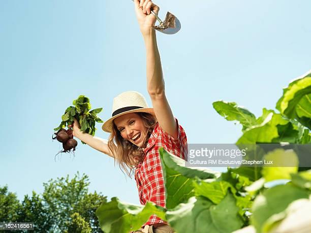 Woman cheering in vegetable garden