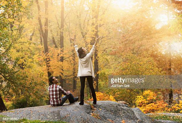 Woman cheering with arms outstretched near boyfriend in park
