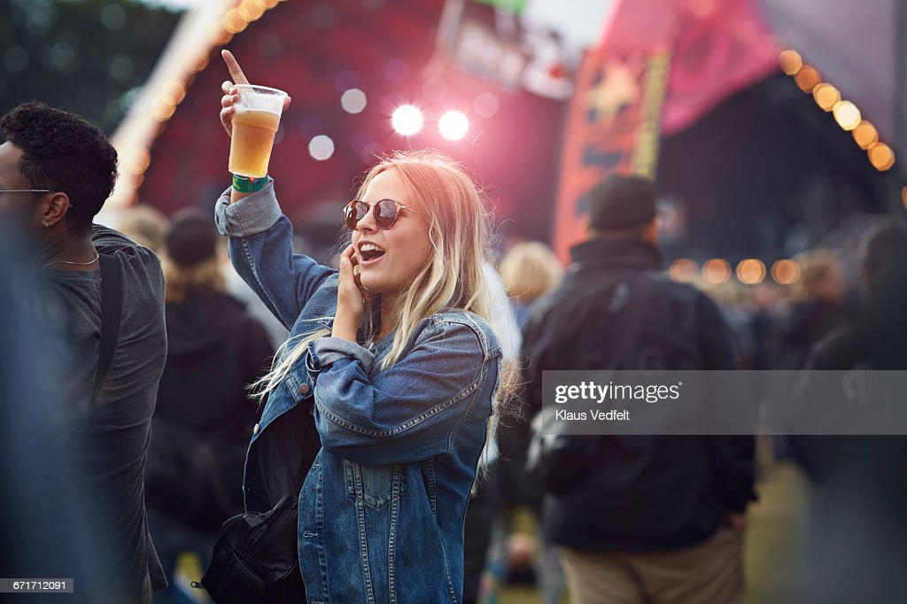 Woman cheering with beer at concert : Stock Photo