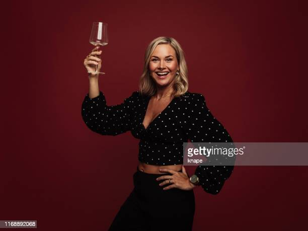 woman cheering with glass of wine in studio against red - holding aloft stock pictures, royalty-free photos & images