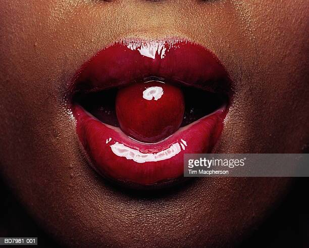 Woman, cherry between lips, detail