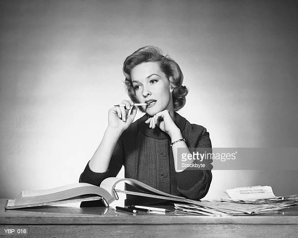 Donna masticare su una matita, libro aperto davanti a lei