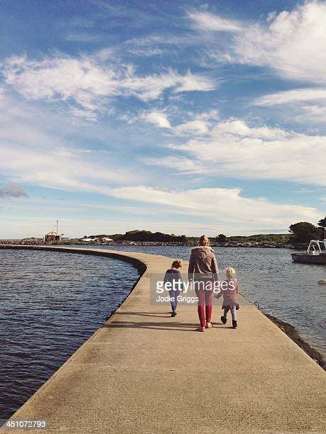 Woman & children walking along breakwater at beach