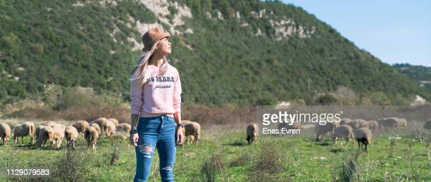 Woman chilling with farm animals in village