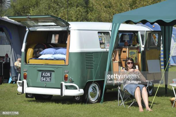 A woman chills out next to her splitscreen VW campervan in the warm sunny weather at the Three Counties Showground Malvern where it is Vanfest...