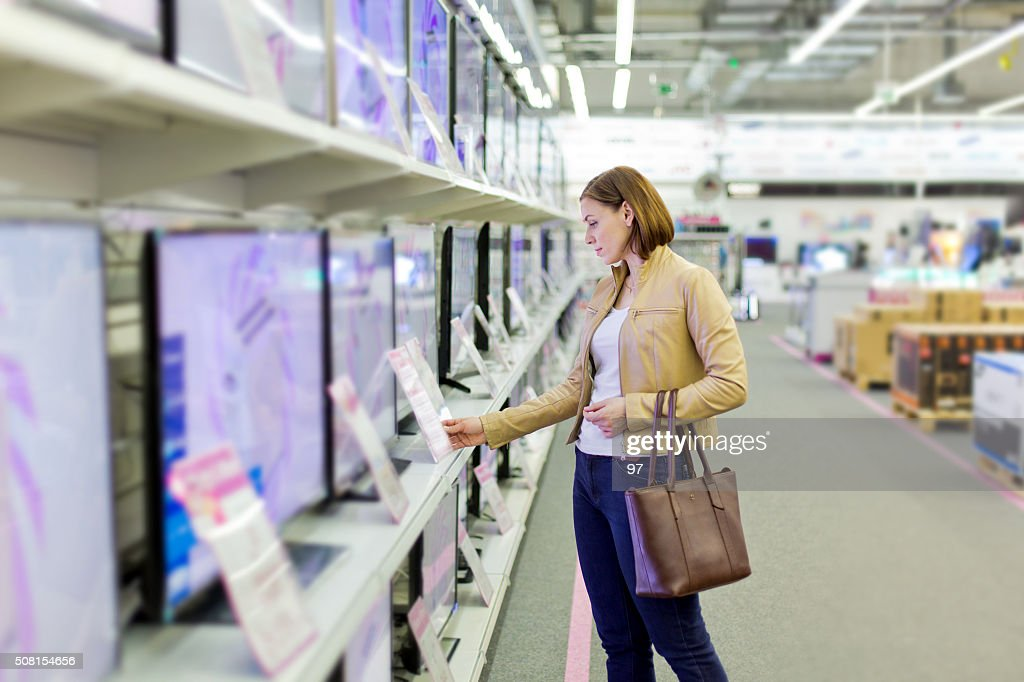 woman chooses a TV in the store : Stock Photo