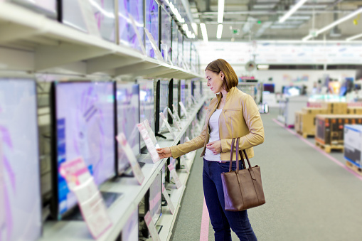 woman chooses a TV in the store 508154656