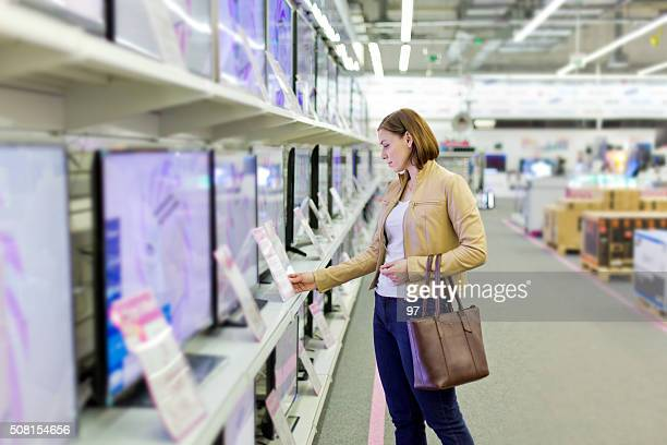 woman chooses a tv in the store - appliance stock pictures, royalty-free photos & images