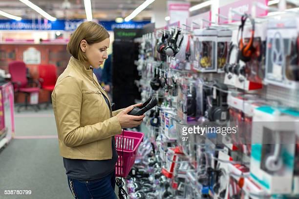 woman chooses headphones store