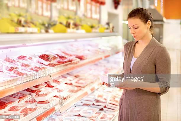 Frau wählt Fleisch im Laden