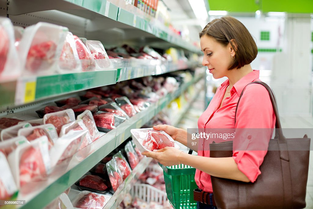 Woman chooses meat in the store : Stock Photo