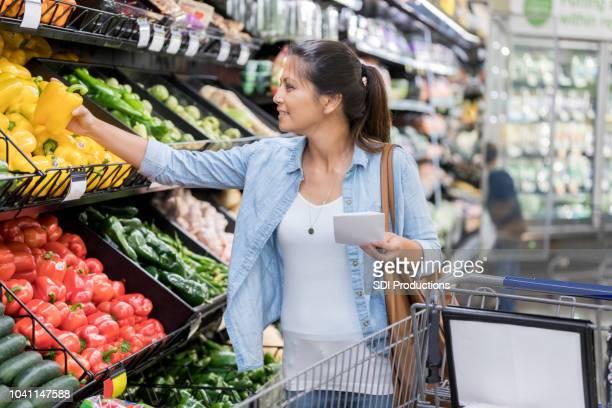 mulher escolhe produtos no supermercado - lista - fotografias e filmes do acervo