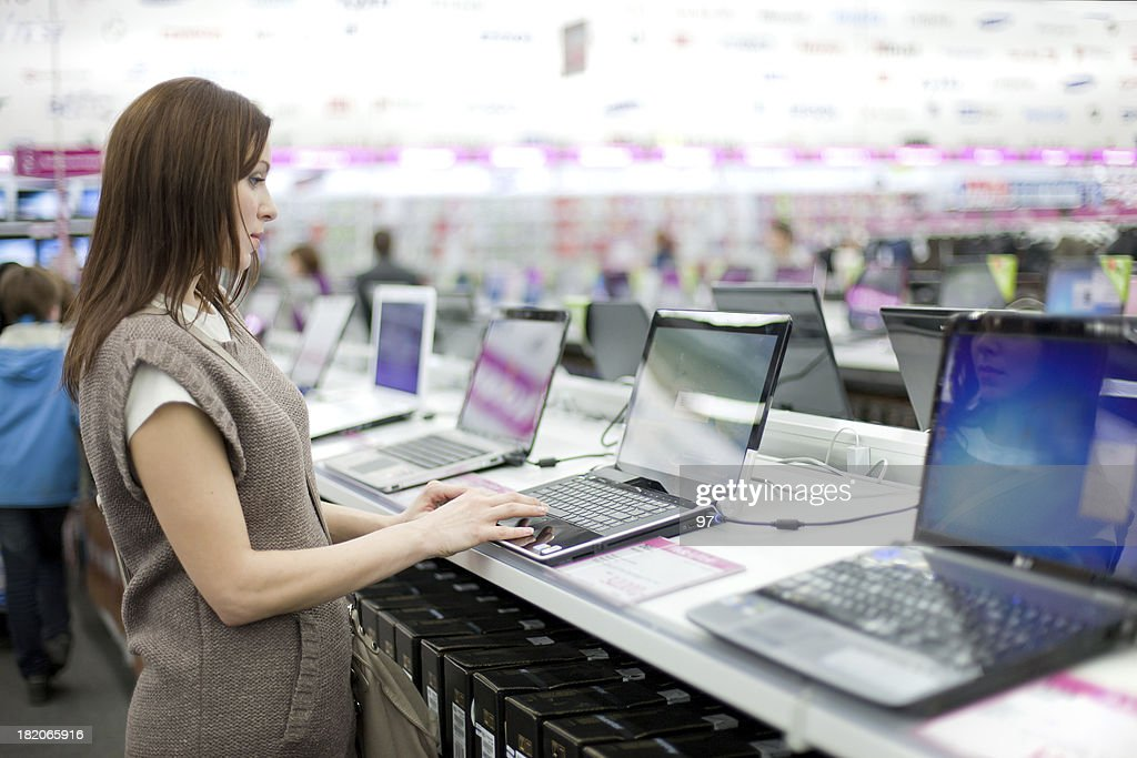 woman chooses the laptop : Stock Photo