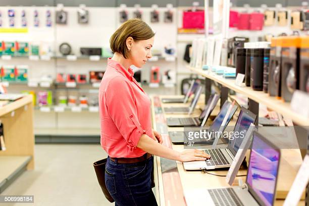 woman chooses the laptop - electronics stock pictures, royalty-free photos & images