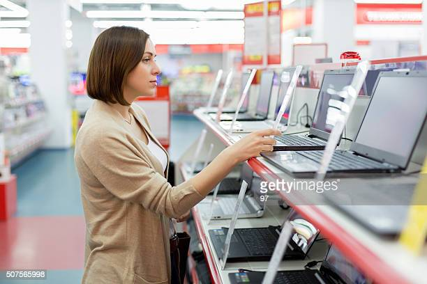 woman chooses the laptop - electronics store stock photos and pictures