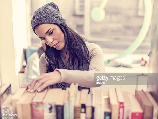 Femme en choisissant le livre dans la bibliothèque.