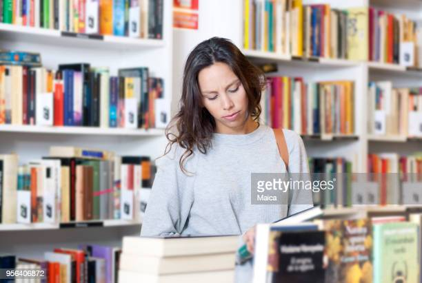 woman choosing a book in the bookstore - book store stock photos and pictures