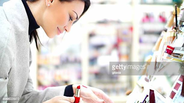 Woman choosing a lipstick at beauty store.
