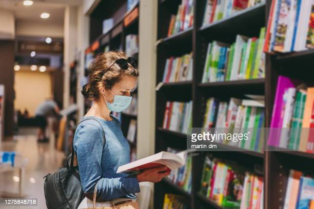 woman choosing a new book in the bookstore during covid-19 pandemic - book shop stock pictures, royalty-free photos & images