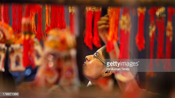 A woman choosing a Rakhi at a roadside shop in Karol Bagh on the eve of Raksha Bandhan on August 19 2013 in New Delhi India The Raksha Bandhan...