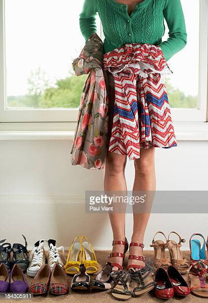 A woman choosing a skirt to go with her shoes