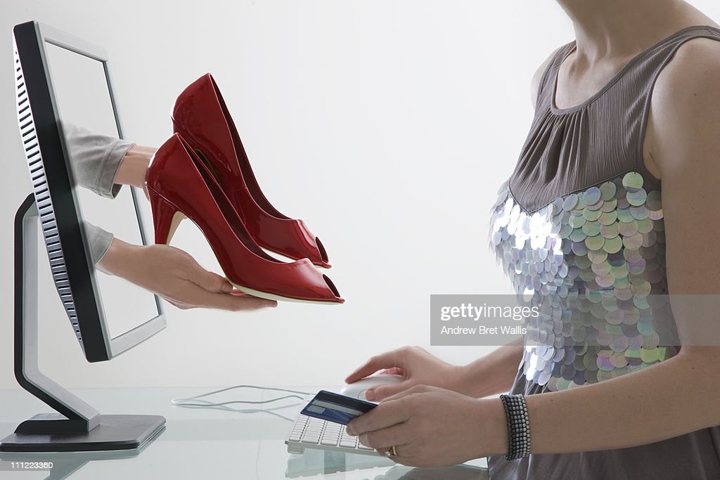 woman choosing and paying for shoes via computer : Stock Photo