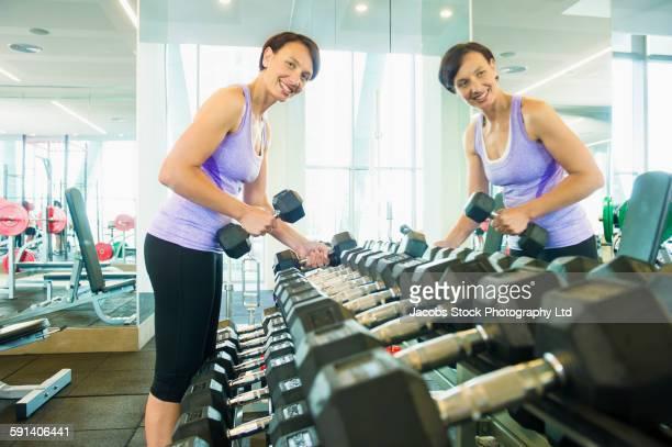 Woman choosing barbell weights in gymnasium