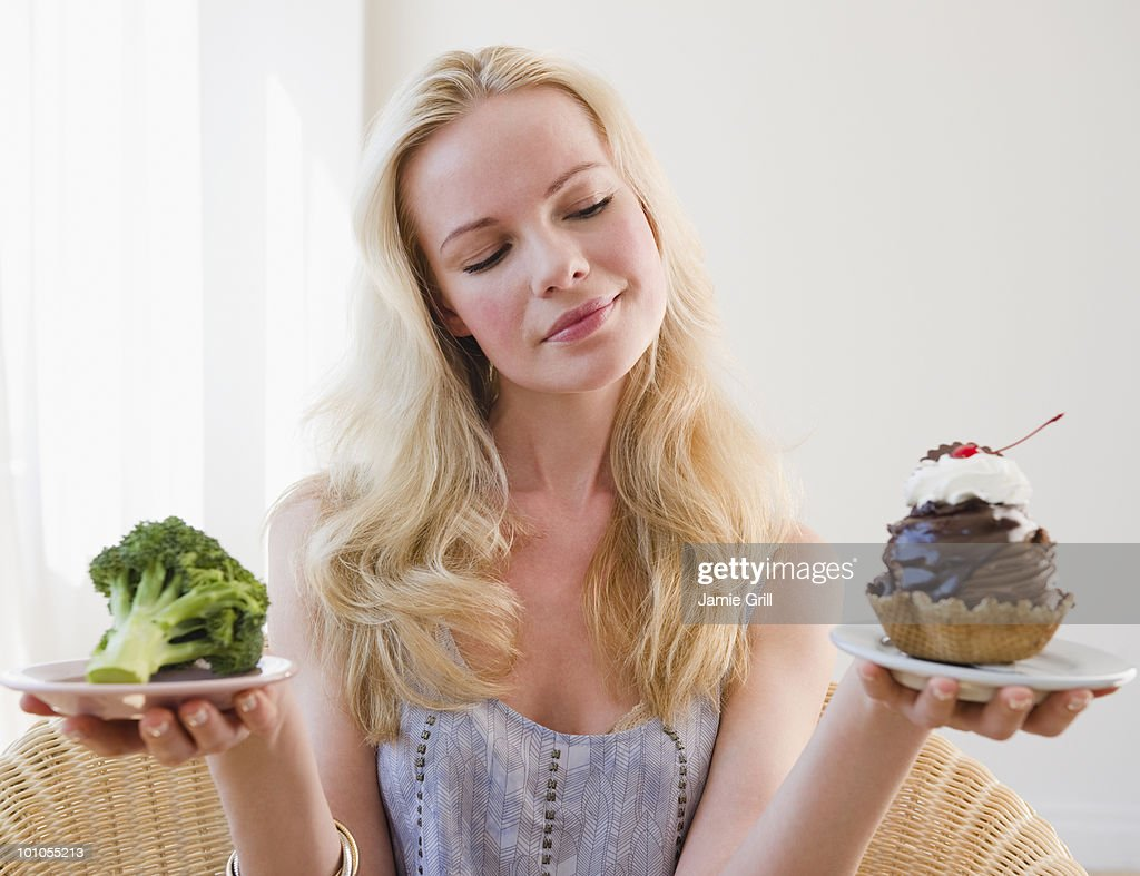 Woman choosing between broccoli or sundae : Stock Photo