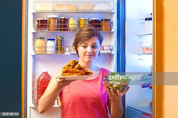 Mulher escolhendo entre alimentos saudáveis e saudável por abrir no frigorífico